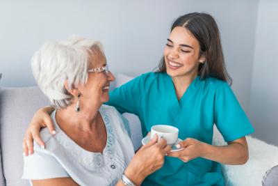 senior woman talking with friendly nurse